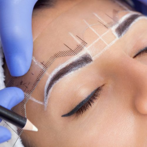 Permanent make-up for eyebrows of beautiful woman with thick brows in beauty salon.